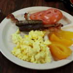 Eggs, Bacon, Sausage, Peaches and Tomatoes